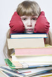 Little cute sad  girl with a pile of book sitting Stock Photo