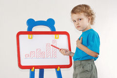 Little cute serious boy drew a diagram of growth Stock Photo
