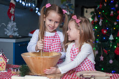 Little cute sisters bake gingerbread cookies for Royalty Free Stock Image
