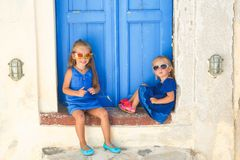 Little cute sisters sitting near old blue door in. Greek village of Emporio, Santorini. This image has attached release Royalty Free Stock Photo