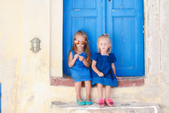 Little cute sisters sitting near old blue door in Stock Photography