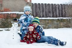 Little cute smiling baby boy and his two older brothers, sitting. Outdoors in the snow, snowman next to them Stock Images