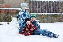 Little cute smiling baby boy and his two older brothers, sitting. Outdoors in the snow, snowman next to them Royalty Free Stock Photo