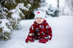 Little cute smiling baby boy, sitting outdoors in the snow. Next to a snowy tree Stock Photos