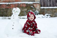Little cute smiling baby boy, sitting outdoors in the snow. Snowman next to him Royalty Free Stock Photography