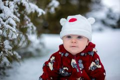 Little cute smiling baby boy, sitting outdoors in the snow. Next to a snowy tree Royalty Free Stock Images