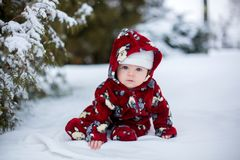 Little cute smiling baby boy, sitting outdoors in the snow. Next to a snowy tree Royalty Free Stock Image