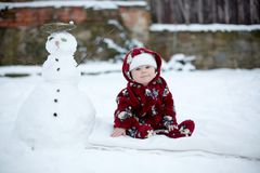 Little cute smiling baby boy, sitting outdoors in the snow. Snowman next to him Stock Photography
