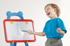 Little cute smiling boy drew a dollar sign. On the whiteboard Royalty Free Stock Image