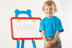 Little cute smiling boy wrote the word mama. On whiteboard Stock Photo