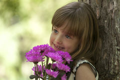Little cute smiling girl in a hat holding a bouquet of flowers. Beautiful little girl holding flowers and enjoy this wonderful gift Stock Photography