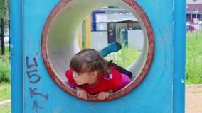Little cute smiling girl play in tube stock video footage