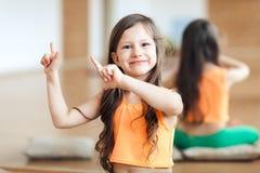 Little cute smiling girl in sportswear posing on camera in orange top, dancing, showing movements with hands. Little cute smiling girl posing on camera in orange stock photography