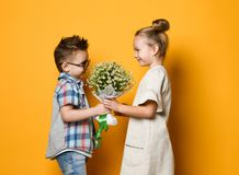Little cute stylish boy gives a bouquet of daisies to his girlfriend blonde girl. romantic photo of a couple. royalty free stock photography