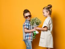 Little cute stylish boy gives a bouquet of daisies to his girlfriend blonde girl. romantic photo of a couple. A date or birthday gift stock photos