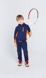 Little cute tennis player in sportswear with racket at studio background. Portrait of happy little boy with tennis racket on white studio background. Young Stock Photo