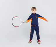 Little cute tennis player in sportswear with racket at studio background. Portrait of happy little boy with tennis racket on white studio background. Young Stock Photography