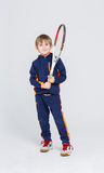 Little cute tennis player in sportswear with racket at studio background. Portrait of happy little boy with tennis racket on white studio background. Young Royalty Free Stock Photo