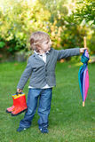 Little cute toddler boy with colorful umbrella and boots, outdoo Stock Photos