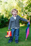 Little cute toddler boy with colorful umbrella and boots, outdoo Royalty Free Stock Image