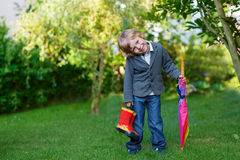 Little cute toddler boy with colorful umbrella and boots, outdoo Stock Photo