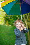 Little cute toddler boy with colorful umbrella and boots, outdoo Stock Photography