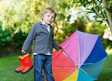 Little cute toddler boy with colorful umbrella and boots, outdoo Royalty Free Stock Photo