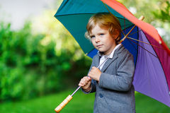 Little cute toddler boy with colorful umbrella and boots, outdoo Stock Images