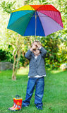 Little cute toddler boy with colorful umbrella and boots, outdoo Stock Image