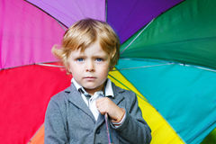 Little cute toddler boy with colorful umbrella and boots, outdoo Royalty Free Stock Photos