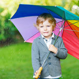 Little cute toddler boy with colorful umbrella and boots, outdoo Royalty Free Stock Images