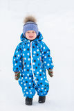 Little cute toddler boy walking outdoors on beautiful sunny winter day.  Stock Photo