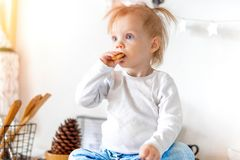 Little cute toddler girl eating oat cookie and sitting on kitchen table. royalty free stock image