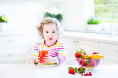 Little cute toddler girl having breakfast drinking juice Stock Image