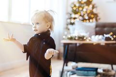 Cute toddler surprised girl in living room. Christmas tree is on background. stock image