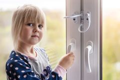 Little cute toddler girl trying to open window in apartment at high-tower building. Children window protection lock. Cable safety guard prevent opening window stock photography