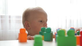 Little cute toddler playing with color blocks stock video