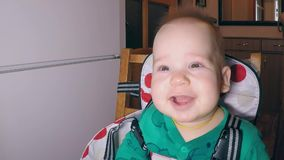 Little cute toothless boy in green body widely smiling sitting in the kitchen in the feeding chair near the refrigerator stock footage