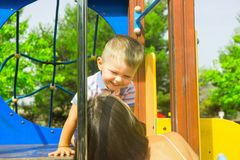 Little cute two year old caucasian toddler boy playing laughing hugging with his mother on playground in city park. Summer day stock images