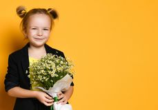 Little cute 5-year-old girl holds a large bouquet of daisies stock photo