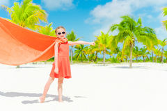 Little cutie girl playing superhero at a tropical beach Stock Images