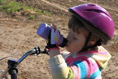 Little cyclist girl drinking Royalty Free Stock Photos