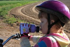 Little cyclist girl drinking Stock Images