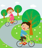 Little cyclists riding their bikes Stock Photos