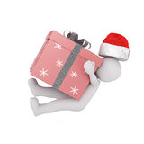 Little 3d man falling under a Christmas gift. Little 3d man wearing a Santa Claus hat falling under the weight of a large red festive a Christmas gift isolated Stock Images