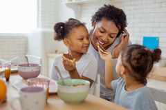 Little dark-skinned girl giving sandwich to her mother. Try it. Cheerful curly-haired women expressing positivity while biting piece of bread stock images