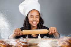 Little dark-skinned girl rolls the dough. The child learns to cook. Clothing and chef hat Stock Photography