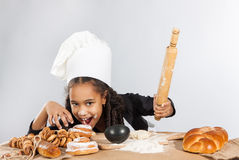 Little dark-skinned girl rolls the dough. The child learns to cook. Clothing and chef hat Stock Images