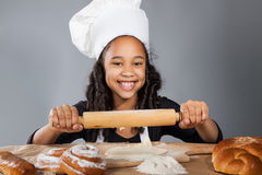 Little dark-skinned girl rolls the dough. The child learns to cook. Clothing and chef hat Royalty Free Stock Photos