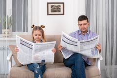 Free Little Daughter And Dad Sitting On The Sofa At Home And Reading The Newspaper Together Royalty Free Stock Images - 144340359